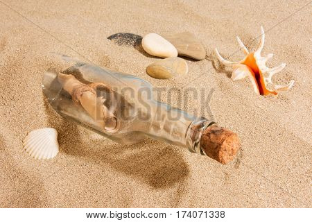 Message in bottle on the beach with seashell