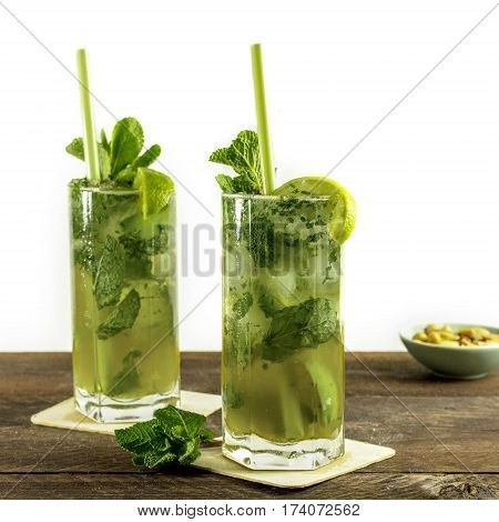 A square photo of mojito cocktails with mint leaves, wedges of lime, drinking straws and a snack, with copy space. Selective focus