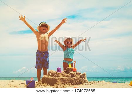 little boy and toddler girl play with sand on tropical beach