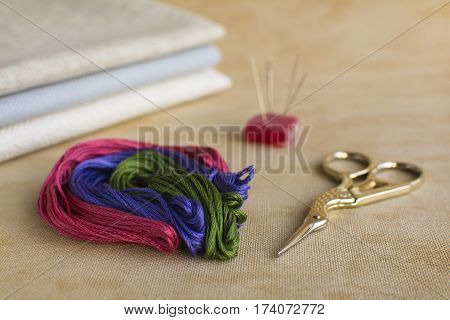 Embroidery and cross-stitch kit on a natural linen background. Scissors needles colored threads and canvas.