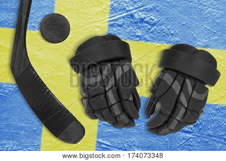 Hockey puck stick gloves and Swedish flag image on the arena ice
