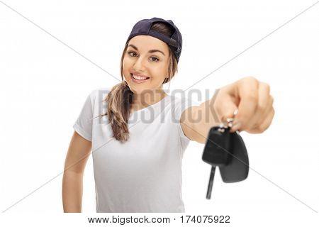 Joyful teenage girl showing a pair of car keys isolated on white background