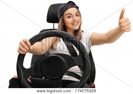 Joyful teenage girl sitting in a car seat and making a thumb up sign isolated on white background