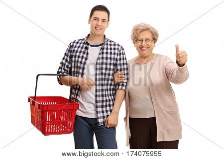 Cheerful guy with an empty shopping basket and a mature lady giving a thumb up isolated on white background