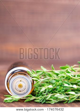 thyme essential oil and dark glass bottle with pipette and fresh thyme on dark brown wooden background. Vertical with copy space.