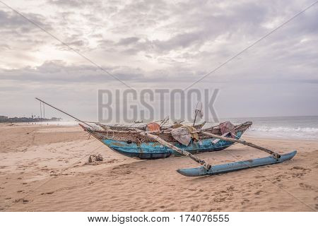 Blue wooden fishing boat on the  sandy beach of the atlantic ocean at the cloudy day.