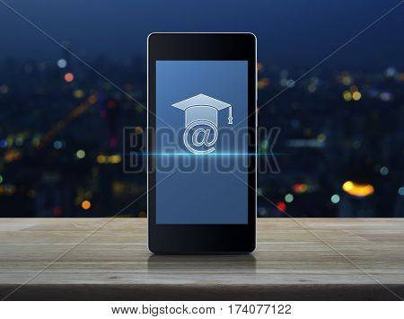 E-learning icon on modern smart phone screen on wooden table over blur colorful night light of city tower Study online concept