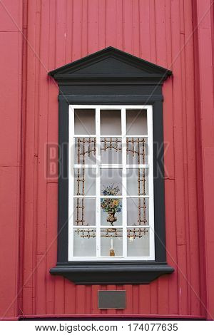 red wall black window curtain vase candle holder