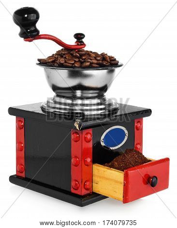 Old antique wooden coffee grinder with coffee beans and ground coffee. Coffee grinder hand-painted in black red and blue. The device isolated on a white background with light shadow and reflection.