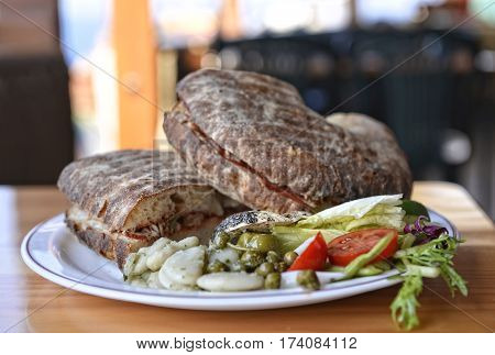 Traditional maltese dish - ftira. Malta food. Typical Maltese bread called ftira accompanied by french fries