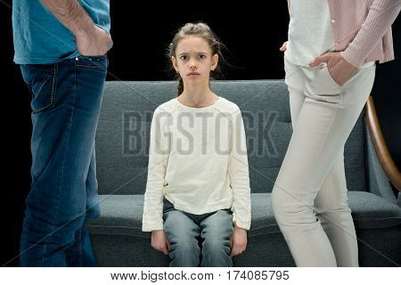 portrait of unsatisfied daughter sitting on sofa with parents near by divorce concept