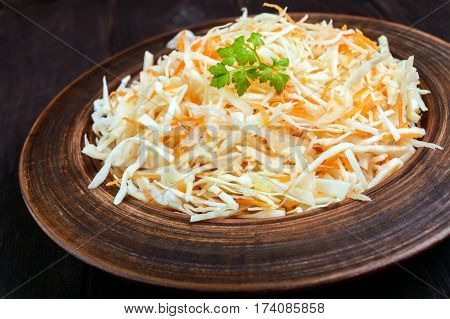 Salad of fresh cabbage and carrots in a clay bowl on dark wooden background. Lean vegetarian vitamin dish. Close up
