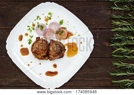 Juicy pork medallions wrapped in bacon on a plate on the dark wooden background. The top view.