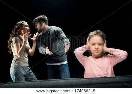Little girl closing ears while parents quarreling family problems concept