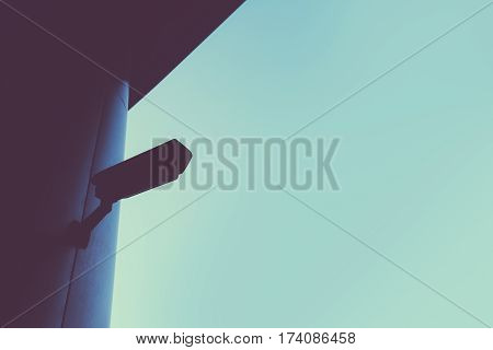 Abstract retro toned silhouette of security camera with blank sky as copy space