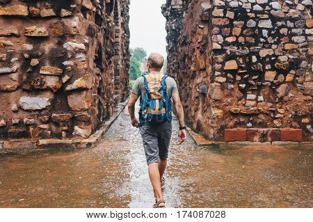 Tourist man walking by the Qutb Minar ruines streets New Delhi India