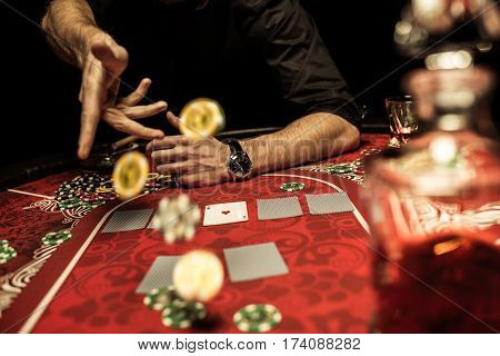 Partial view of man throwing poker chips on table while playing poker