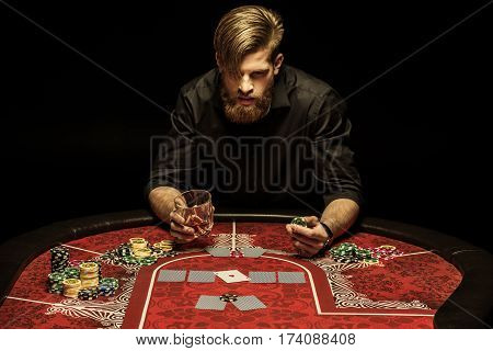 Bearded man with glass of alcohol drink and poker chip in hands sitting at poker table