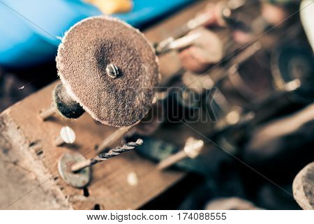 Rotary tool attachments in a workshop on a handmade wooden holder closeup.