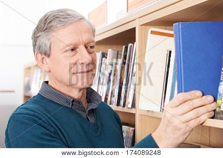 Mature Male Student Taking Book From Library Shelf