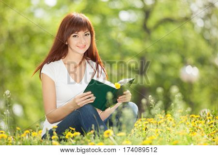 Young woman reading a book in the park with flowers. Beauty nature scene with colorful background, trees and flowers at spring season. Outdoor lifestyle. Happy smiling woman relax on green grass