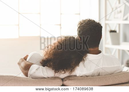 Back view of happy Afro American couple are hugging while sitting together on sofa at home