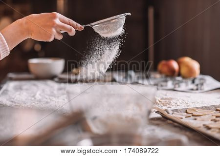 'Close-up partial view of human hand sifting flour above kitchen table