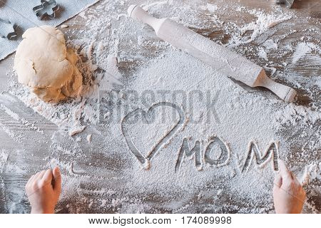 'Partial top view of child drawing heart symbol and word mom in flour on table Mothers day concept