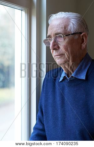 Senior Man Suffering From Depression Looking Out Of Window