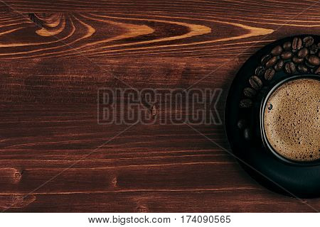 Hot coffee in black half cup with crema and beans with copy space on brown old wooden board background top view. Rustic style.