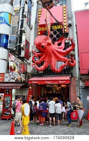 People Stand In Row For Buy Takoyaki From Takoyaki Shop At Dotonbori Street