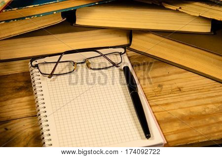 Notepad fountain pen and glasses in front of many books