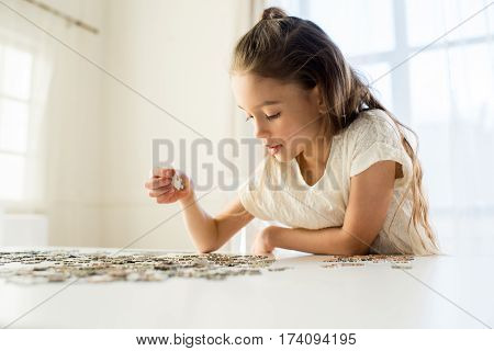 side view of concentrated little girl playing with puzzles at home