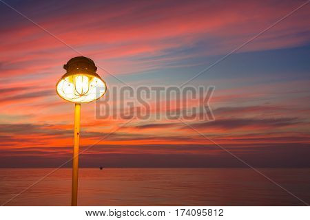 Lighting of warm lamp or yellow HID lamp and lighting of sunset at sea with beautiful sky and clouds in the evening with twilight time and silhouette on offshore platform.