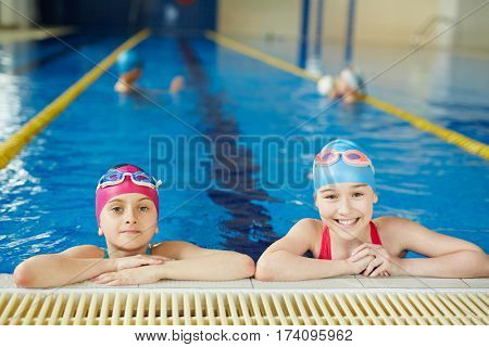 Portrait of two schoolgirls smiling and looking at camera at pool swimming practice
