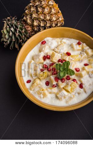 ananas or anaanaas or pineapple raita, chopped pieces of pineapple mixed with sweet curd and garnished with pomegranate and mint, favourite side dish or starter food in India