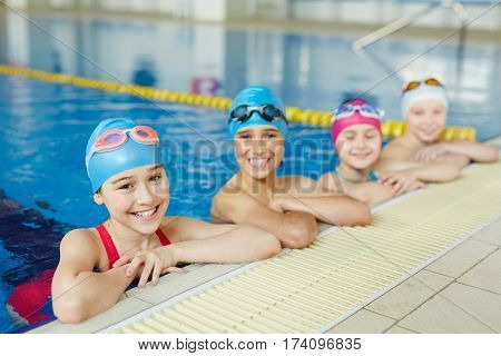 Group of joyful school kids smiling looking to camera at border of swimming pool during practice