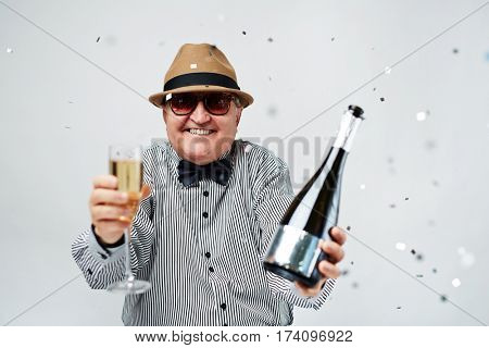 Waist-up portrait of excited elderly man in bowler hat and sunglasses cheering with bottle of champagne and confetti