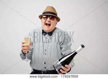 Waist-up portrait of dressed-up retired man holding a bottle of champagne and laughing cheerfully with his mouth wide open