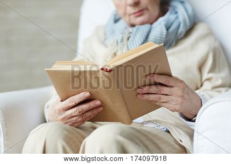 Wrinkled female hands holding thick book with brown cover, close-up shot