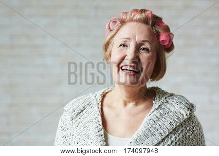 Joyful elderly woman with hair curlers standing against white brick wall and looking away with toothy smile