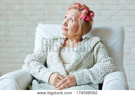 Portrait of dreamy senior woman with hair rollers and in warm knitted cardigan sitting on white armchair and looking upwards with smile