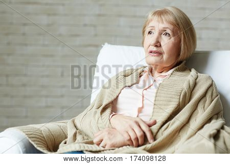 Waist-up portrait of pensive blond-haired senior woman in pale pink blouse sitting on comfortable couch and covered her shoulders with brown plaid