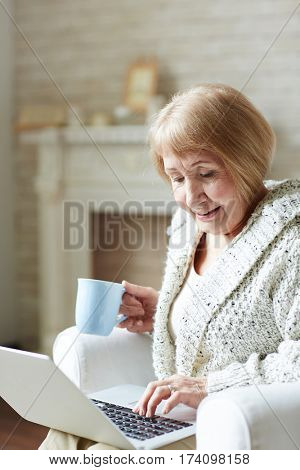 Modern granny sitting at home with cup of coffee and chatting with her granddaughter via social networking site, fireplace decorated with mementos observed behind her