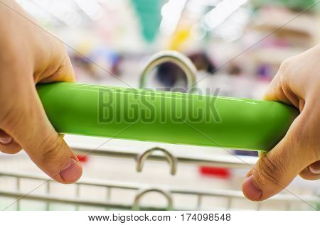 Woman pushing green shopping cart in store, close-up