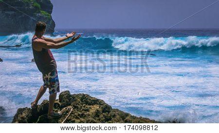 Man Provoke Ocean Waves on Tembeling Coastline at Nusa Penida island, Bali , Indonesia