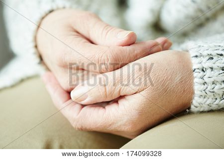 Close-up shot of wrinkled female hands lying on laps of senior woman