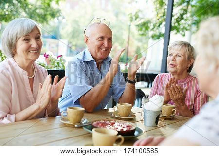 Group of smiling elderly people gathered together in outdoor cafe for tea-drinking and applauding joyfully