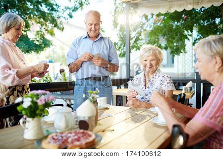 Joyful elderly people hanging out in summer cafe: they drinking tea with delicious pie and playing cards