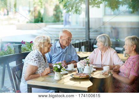 Four childhood friends gathered together in outdoor cafe after long separation and remembering funny stories from their past